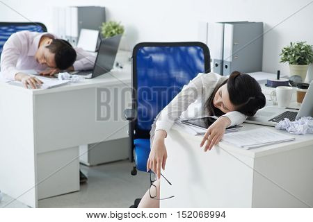Exhausted Asian business people sleeping in office