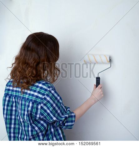 Young woman in casual clothes in front of white unpainted wall working with paint roller, happy people and construction concept