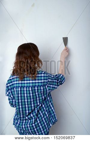 Young woman in casual clothes in front of white unpainted wall working with putty knife, happy people and construction concept