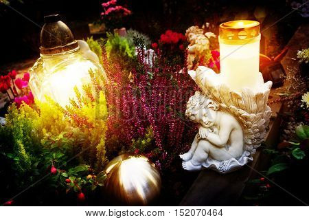 Grave decoration in autumn with angels and tomb candles