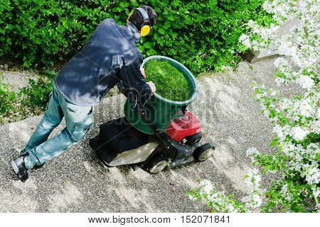 Houilles, France - April 08, 2014 : Gardener mowing the lawn in a park