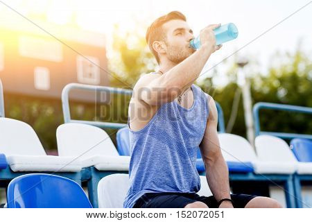 Sports man drinking water after exercising on outdoors stadium. Image with lens flare effect