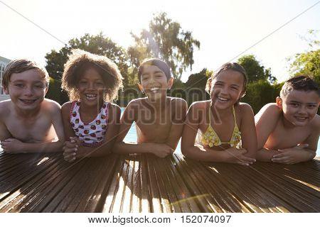 Portrait Of Children Having Fun In Outdoor Swimming Pool