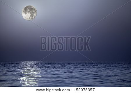 Light from the moon reflecting off a calm blue sea at the horizon. Serene composite image with plenty of natural copy space.