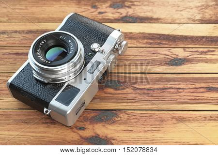 Modern mirrorless camera stilized to retro vintage film camera on wood table background. 3d illustration