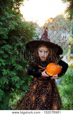 Halloween. The girl of 7-8 years represents the angry sorcerer. She is dressed in a dark dress and a hat and holds orange pumpkin lamp. The girl has an angry facial expression.