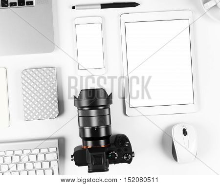 Top view on photographer workplace: Keyboard, tablet, camera and smartphone on white desk background.