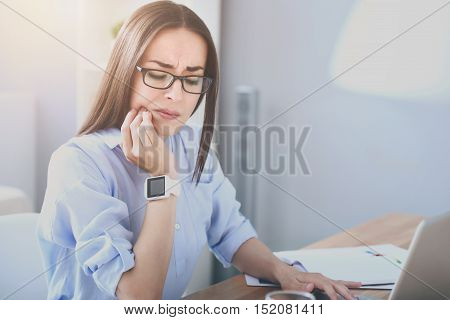 Unbearable toothache. Good looking bespectacled woman working on laptop and having toothache while sitting by the table.