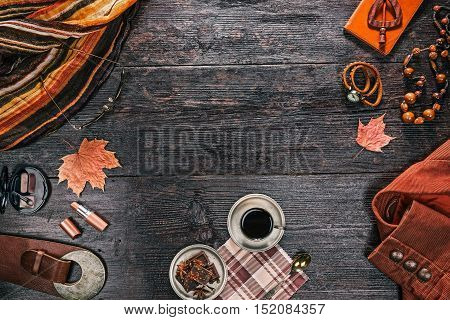 Autumn outfit of female apparel and accessories with cup of coffee and spicy chocolate on dark wood surface. Flat lay