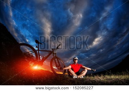 Man Cyclist Is Engaged In Yoga On A Sunset