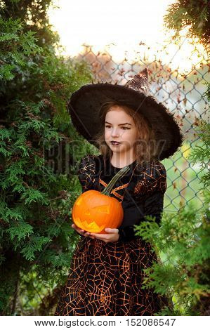 Halloween. Beautiful little girl portrays the evil fairy. She is wearing a dark dress and a hat. On her face make-up. In the hands of the girl Jack-o-lantern. Children adore Halloween.