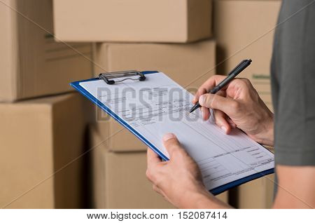 Warehouse manager signing dispatch sheet. Close up hand of manager checking delivery order. Young freight manager checking invoice with cardboard box parcel.