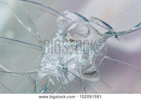 Firearms bullethole on the glass from the bullets cracks and broken background. Criminal concept