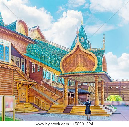 The scenic wooden porch of the Grand Palace of Alexei Mikhailovich with carved pillars and complex green canopy located in Kolomenskoye Moscow Russia.