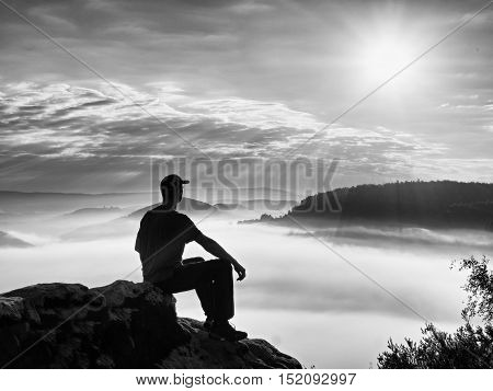 Alone Hiker In Black Trousers And Red Shirt  And Red Cap Sit On Cliff's Edge A