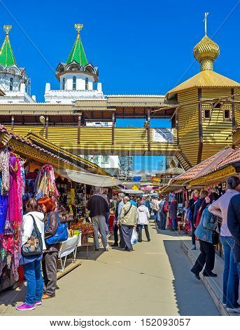 MOSCOW RUSSIA - MAY 10 2015: The crowded souvenir row of Izmailovsky Market with the timbered church and covered gallery on the background on May 10 in Moscow.