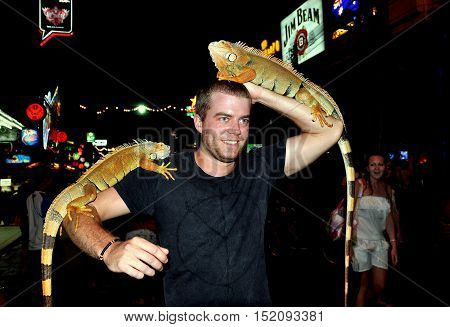 Phuket Thailand - January 2 2012: Tourist poses with two large iguana lizards for photos on funky Bangla Road