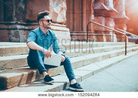 Enjoy every day. Positive content smiling young man holding tablet and expressing joy while sitting on the footsteps