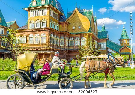 MOSCOW RUSSIA - MAY 10 2015: The ride on fiacre with the coachman dressed in old-style traditional costume around the wooden Grand Palace in Kolomenskoye on May 10 in Moscow.
