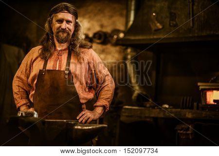 Senior blacksmith in smithy.