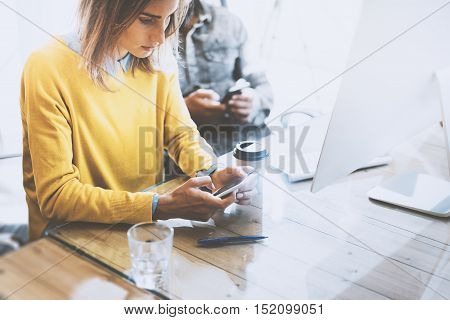 Coworking process in a sunny office.Woman using mobile phone at the wood table.Man typing on his smartphone.Horizontal photo, blurred background
