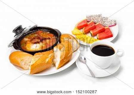 Pork braised in sweet and sour sauce with eggs and bread in an Asian style with coffee and fruit salad on white