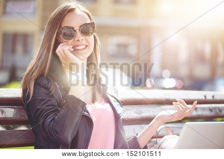 Call me back. Positive charming young woman smiling and talkign on cell phone while having a walk