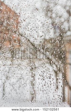 Texture of the ice and drops on the window glass in inclement winter weather close up
