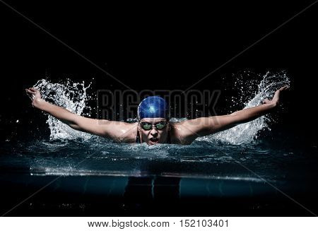 Profesional woman swimmer swim using breaststroke technique on the dark background