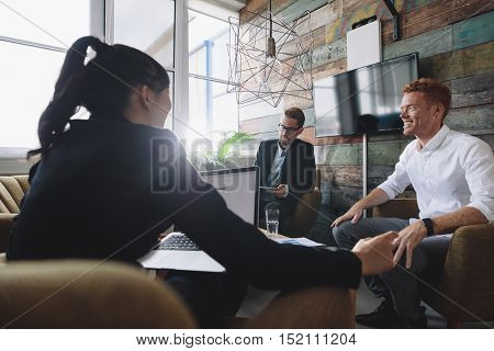 Young man sitting in discussing business with colleagues. Business professionals in meeting room.