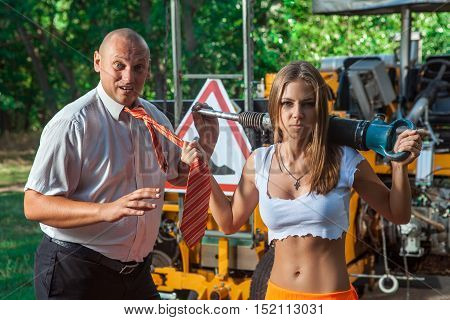 Sexy woman worker in overalls with the jackhammer is holding boss tie.