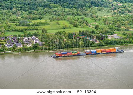 Spay Germany - May 23 2016: Container ship on the Rhine River Rhine Valley UNESCO World Heritage Site Germany. Spay is a municipality in the district of Mayen-Koblenz in Rhineland-Palatinate western Germany.