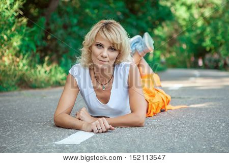 Sexy Woman Worker In Overalls Is Laying On The Road.