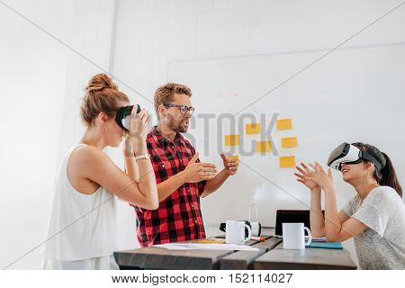 Team of developers working with virtual reality glasses during a business meeting. Young man with female colleagues brainstorming on augmented reality technology devices.