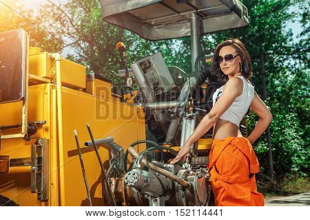 Sexy Woman Worker In Overalls Is Standing Near The Tractor.
