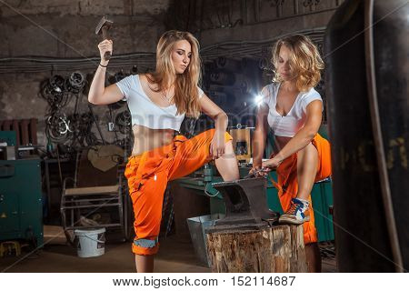 Sexy Blacksmith Women In Orange Pants Are Working With The Hummer And Anvil.