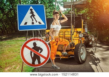 """Woman In Orange Overalls Is Mounting """" No Men"""" Signs On The Road."""