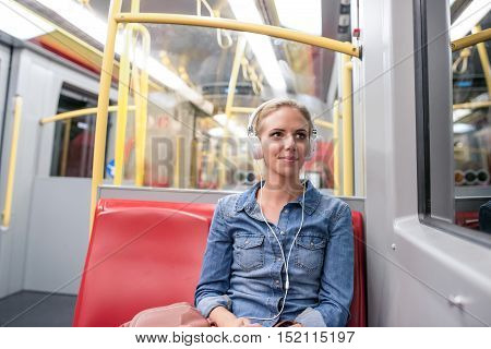 Beautiful young blond woman in denim shirt sitting in subway train with white headphones listening music
