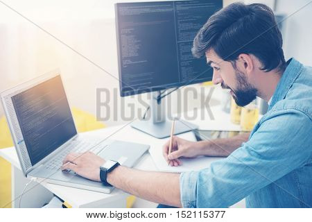Note it. Concentrated handsome young man coding on a laptop while noting something and working as a programmer in an office
