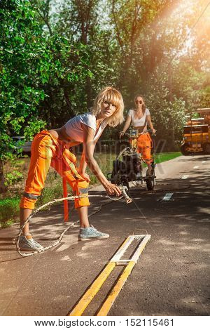 Woman worker is drawing a road marking with the airbrush.