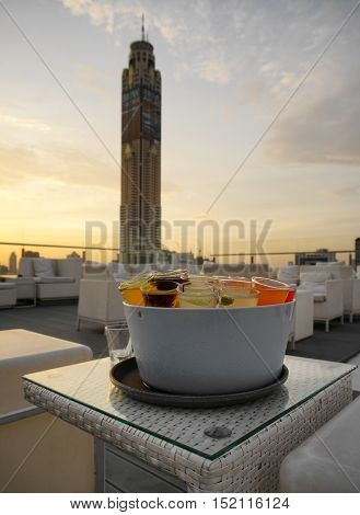 various cocktail shot course serve in ice bucket in evening twilight time with blur focus of open air rooftop bar  - soft focus,sihouettes