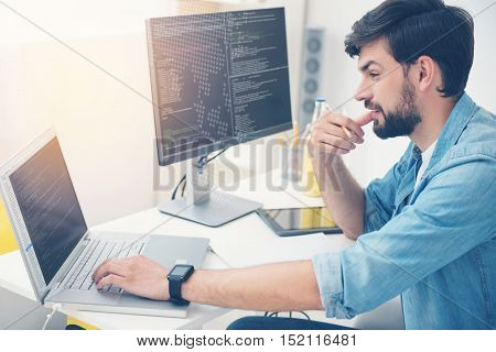 Have it done. Young concentrated ambitious man working in an office as programmer while coding and writing a program