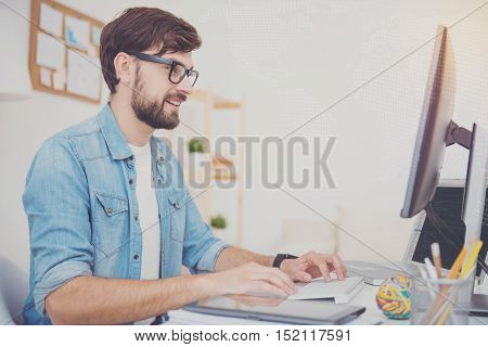Happy to work. Delighted young handsome programmer using a computer while working and sitting in an office.