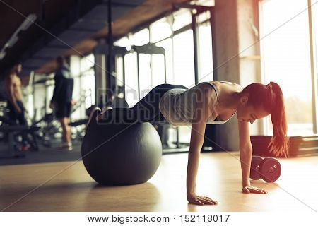 Beautiful young woman training pilates in gym