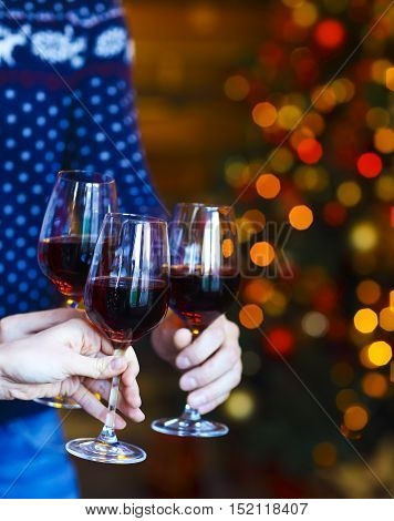 Clinking glasses of red wine in hands on Christmas lights background. X-mas party concept