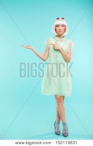 Full length of attrative blonde young woman standing and holding copyspace on palm