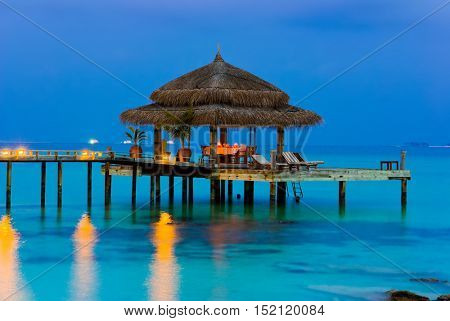 Water cafe at evening, lights, ocean and sky
