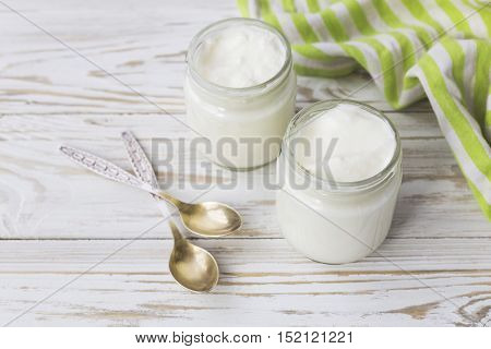 Homemade Yogurt In Glass Jar On Wooden Table.