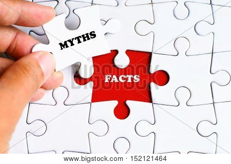 """FACTS"" word on missing puzzle with a hand hold a piece of ""MYTHS"" word puzzle want to complete it - business and finance concept poster"