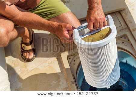 Cognac, France - July 22, 2013: A retired man in shorts and topless takes care of the maintenance of his private swimming pool. Control filtration system pool